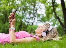 Jeune femme écoutant la musique tout en fixant sur l'herbe Photographie stock libre de droits