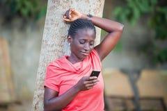 Jeune femme écrivant le texte à un téléphone portable image stock