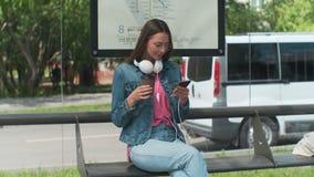 Jeune femme élégante attendant le café de transport en commun et de boissons tout en se tenant à la station moderne de tram dehor banque de vidéos
