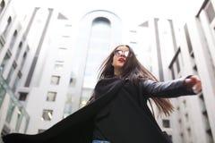 Jeune femme élégante avec de longs cheveux en verres marchant au CIT image stock