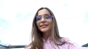 Jeune femme élégante dans des lunettes de soleil souriant contre le ciel, prenant le selfie, jeunesse photographie stock libre de droits