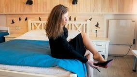 Jeune femme élégante dans la robe noire se reposant sur le lit à la chambre d'hôtel et enlevant des chaussures photo libre de droits