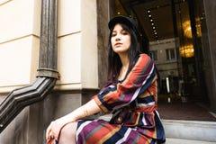 Jeune femme élégante dans une robe rayée multicolore et un chapeau noir images libres de droits