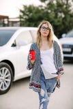 Jeune femme élégante dans une rue de ville près d'une voiture blanche Image libre de droits