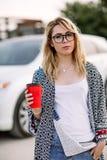 Jeune femme élégante dans une rue de ville près d'une voiture blanche Image stock