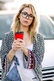 Jeune femme élégante dans une rue de ville près d'une voiture blanche Photographie stock libre de droits