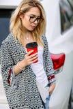 Jeune femme élégante dans une rue de ville près d'une voiture blanche Images libres de droits
