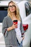 Jeune femme élégante dans une rue de ville près d'une voiture blanche Photo stock