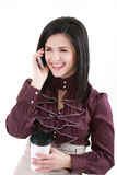 Jeune femme élégante de brune avec du café parlant par l'isolant de téléphone Images stock