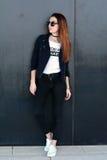 Jeune femme élégante de gingembre se tenant prêt le mur sur la rue Séance photos de mode Photos stock