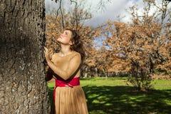 Jeune femme élégante de portrait recherchant un arbre aspirational ambiant image libre de droits