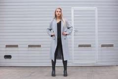 Jeune femme élégante portant le manteau gris posant contre le mur rugueux de rue, style urbain minimaliste d'habillement image libre de droits