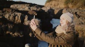 Jeune femme élégante prenant des photos de selfie sur le smartphone La femelle de déplacement saisit des souvenirs heureux et la  banque de vidéos