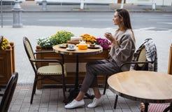 Jeune femme élégante prenant un petit déjeuner français avec du café et le gâteau se reposant à la terrasse de café images stock