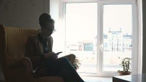 Jeune femme élégante s'asseyant dans l'espace coworking et à l'aide du smartphone, surfant l'Internet du téléphone portable banque de vidéos