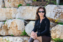 Jeune femme élégante s'asseyant dehors sur des pierres Photographie stock libre de droits