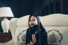 Jeune femme élégante s'asseyant sur le sofa blanc image stock
