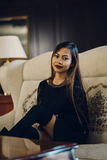 Jeune femme élégante s'asseyant sur le sofa blanc photo stock