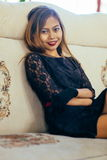 Jeune femme élégante s'asseyant sur le sofa blanc Image libre de droits