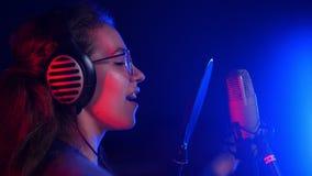 Jeune femme émotive dans des écouteurs chantant dans le studio Éclairage au néon banque de vidéos
