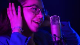 Jeune femme émotive dans des écouteurs chantant dans le studio Éclairage au néon pourpre banque de vidéos