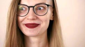 Jeune femme émotive espiègle avec de longs cheveux blonds et verres Il regarde à gauche et à droite, des rires heureusement, rega clips vidéos
