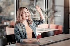 Jeune femme émotive saluant son ami dans un café Photos libres de droits