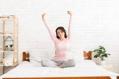 Jeune femme énergique chantant et dansant dans le lit photos stock