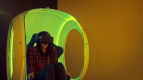 Jeune femme éprouvant la réalité virtuelle se reposant dans la chaise mobile interactive