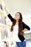 Jeune femme étirant le bras vers l'étagère supérieure Photos stock