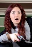 Jeune femme étonnée avec l'extérieur de TV Photo stock