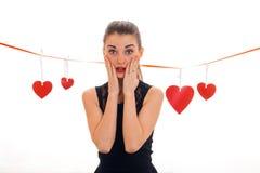 Jeune femme étonnée de brune avec les lèvres et les coeurs rouges sur le fond d'isolement sur le blanc Photos stock