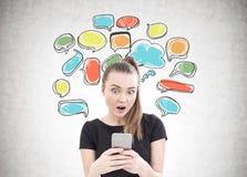 Jeune femme étonnée, smartphone, bulles de la parole Photo stock