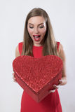 Jeune femme étonnée tenant un grand jour de valentine de présent de coeur Photo stock