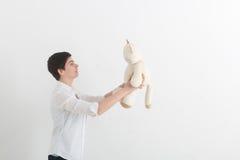Jeune femme étrange avec les cheveux courts dans la chemise blanche parlant à son chat de peluche de jouet sur le fond gris-clair Image libre de droits