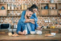 Jeune femme étreignant l'homme barbu à l'aide du smartphone pendant le petit déjeuner images stock