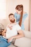 Jeune femme étreignant l'homme barbu bel s'asseyant sur le sofa à la maison Photographie stock libre de droits