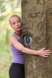 Jeune femme étreignant un arbre Image stock