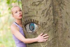 Jeune femme étreignant un arbre Images stock