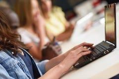 Jeune femme étudiant avec l'ordinateur portable sur le bureau blanc Images libres de droits