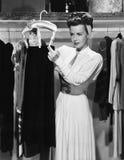Jeune femme accrochant vers le haut d'une jupe dans le cabinet (toutes les personnes représentées ne sont pas plus long vivantes  photographie stock