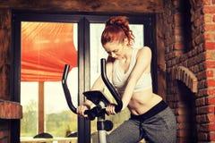 Jeune femme active faisant l'exercice sur la bicyclette à la maison photographie stock libre de droits