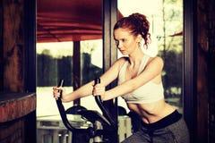 Jeune femme active faisant l'exercice sur la bicyclette à la maison image libre de droits