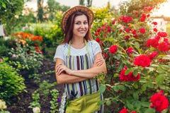 Jeune femme admirant son jardin d'été Jardinier dans le tablier et chapeau regardant des fleurs passe-temps photos libres de droits