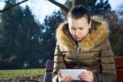 Jeune femme/adolescent employant la séance extérieure de comprimé sur le banc et Image stock