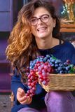 Jeune femme - adolescente avec de longs, onduleux cheveux, verres de port, tenant des raisins, sourire, se reposant sur les escal Images libres de droits