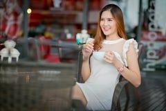 Jeune femme - adolescente s'asseyant dehors aux WI de table de café Image stock