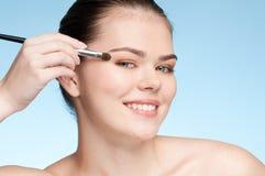 Jeune femme adulte appliquant le balai cosmétique d'ombre photo stock