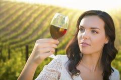 Jeune femme adulte appréciant un verre de vin dans le vignoble photographie stock libre de droits