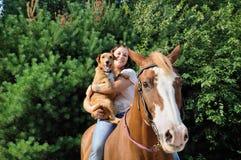 Jeune femme adulte avec son cheval et crabot Images stock